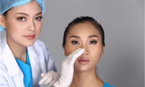 A surgeon attending to her patient for a nose job.